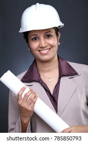 Young female architect holding blue print