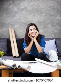 The young female architect working on project,with smile and happy face,rest the chin on hands,plenty of architect drawing paper on table,white safety helmet beside her,working hour.