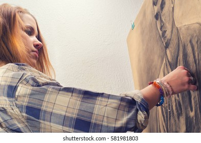 Young female artist drawing portrait of young man using charcoal.