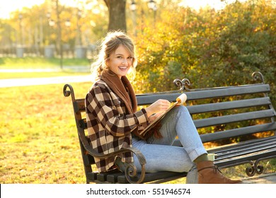 Young female artist drawing sketch while sitting on bench in beautiful park