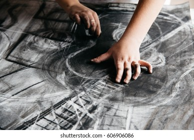 Young female artist painting with charcoal on paper