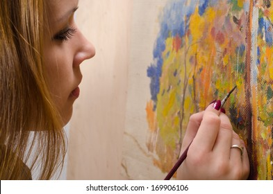 Young female artist painting in her studio.