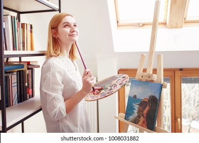 Young female artist painting in home studio. Blond girl in white short in white room with wooden windows