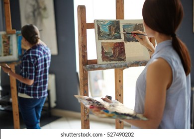 Young female artist painting natural scenes
