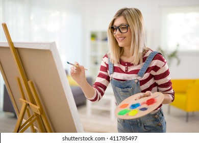 Young female artist painting on a canvas with a paintbrush and holding a color palette at home