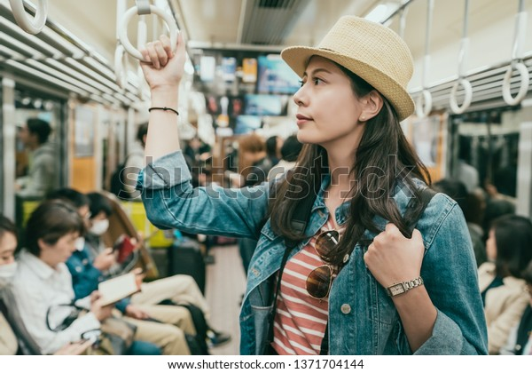 地下鉄の電車の中でハンドルを持つアジアの若い女性の手。日本の大阪では、麦藁帽をかぶった優雅な女性が公共交通で通勤する。地下鉄で静かに座る座席を持つ人々