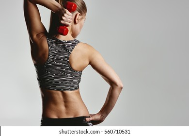 Young female athlete doing lifting exercise with dumbbell. Concept of health and body care.
