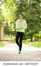 Young female athlete is exercising outdoors. She is jogging in a park.
