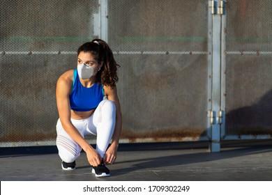 Junge weibliche Sportlerin mit Gesichtsmaske zum Schutz vor Covid-19-Ansteckung, die sich auf das Laufen in der Stadt und das Fitnesstraining vorbereitet. Motivierte Frauen, die sich draußen unter einer Krise der Koronavirus-Gesundheit fortbilden.