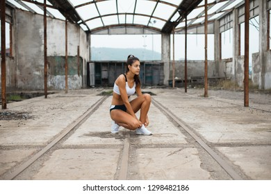 Young female athlete getting ready for outdoor running workout. Sporty girl lacing footwear at old industrial ruins.
