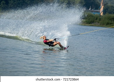 young female athlete glides on water skis on the waves on the lake