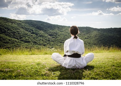 Young female athlete in karate kimono sitting on a field. Martial arts.