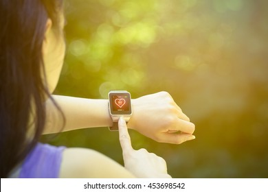 Young female athlete looking at heart rate app and checking beats per minute on her smart watch in the park. Fitness, healthy lifestyle and new technology concepts.