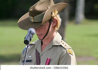 Young female Australian Army officer (soldier) wearing medal and iconic Slouch Hat gives emotional speech during ANZAC rememberance service in front of Australian flags on the Gold Coast, Australia.