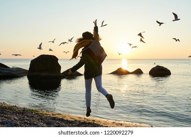 Young female in autumn outfit having fun by the sea at sunrise or sunset