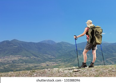 A young female with backpack and hiking poles in the mountain