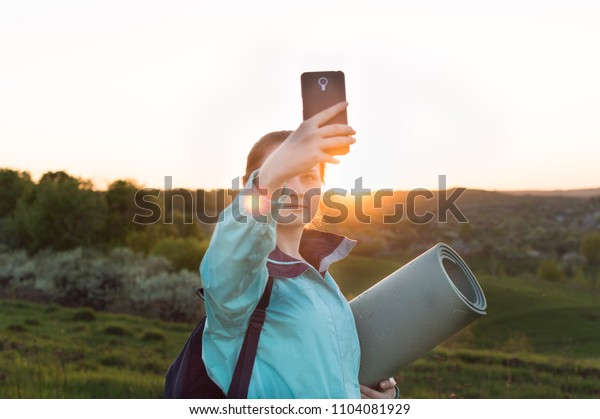 Young female backpacker with tourists mat making selfie on the sunset. Concept of the vacation, travel, enjoyment, blogging, vlogging.