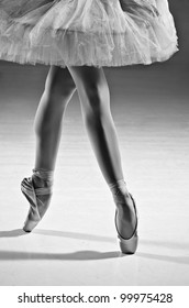 Young female ballerina standing on toes, low section
