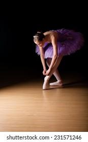 Young female ballerina wearing a lilac colored tut adjusting her shoes against black background