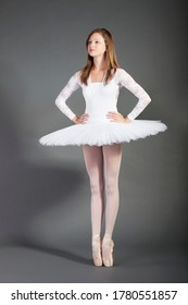 Young female ballet dancer tiptoeing against grey background