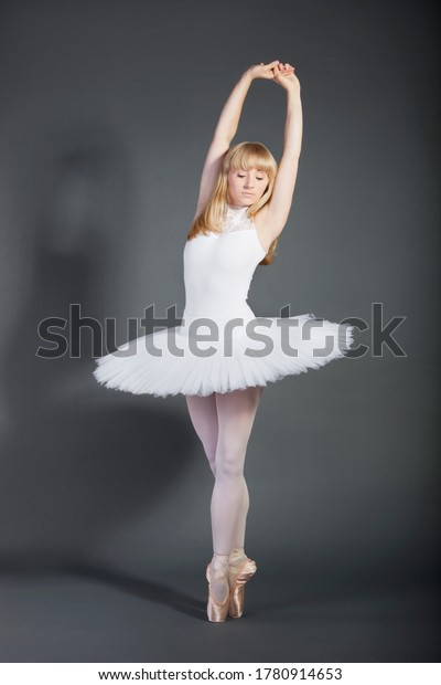 Young female ballet dancer tiptoeing over grey background
