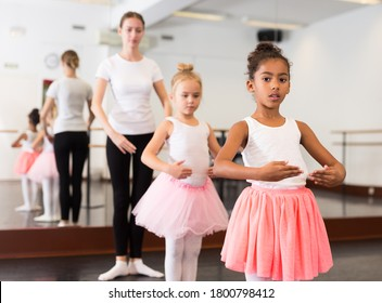 Young female ballet teacher and two little girls in classical dance school