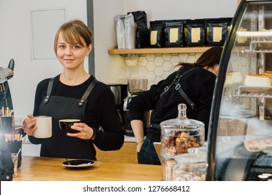 Young female barista in black uniform pouring milk while making cappuccino. Skillful staff and team work concept. Close up