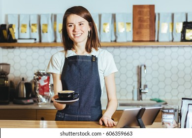 Young female barista holding cup of cappuccino and standing behind the bar in cafe smiling. Coffee culture concepts with real people models.
