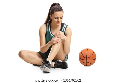 Young female basketball player sitting on a floor and holding her painful knee isolated on white background