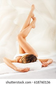 Young female with beautiful clean legs in underwear lying on bed and relaxing.Beauty and body care concept.