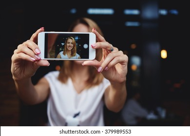 Young female with beautiful smile photographing herself on mobile phone for social network pictures, charming woman making self portrait with cell telephone camera while relaxing in modern coffee shop
