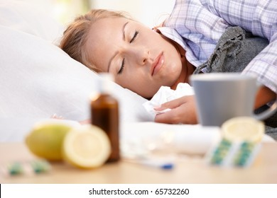 Young female in bed at home caught cold, feeling bad, taking medicines and vitamins, sleeping.?