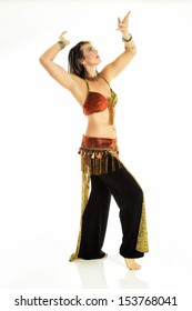 Young female belly dancer in a red and gold outfit with black pants. Isolated on white.