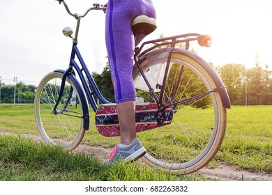 Young female biker next to her bike in a park. Unrecognizable attractive young adult female with bike, cycling or commuting, ecological transportation concept. Closeup attractive beautiful woman.