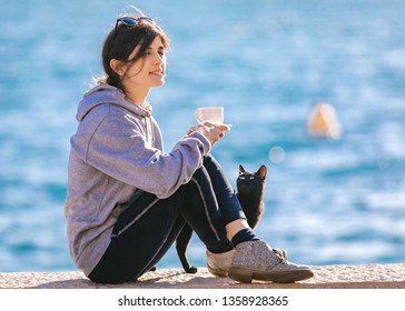 Young female with black cat enjoying in coffee near the sea.