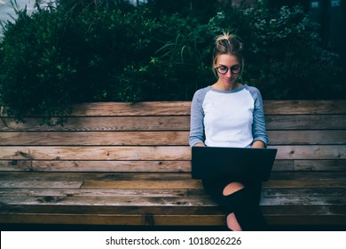 Young female blogger chatting with followers and sending feedbacks resting on bench in town with netbook,hipster girl working on freelance using laptop computer enjoying spending time outdoors