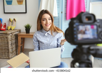 Young female blogger with laptop and book on camera screen