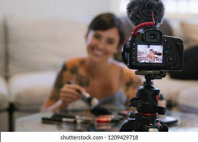 Young female blogger recording vlog video on camera with makeup cosmetic at home. Focus on tripod mounted camera screen showing female fashion blogger reviewing make up products.