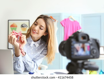 Young female blogger with tie bow recording video at home