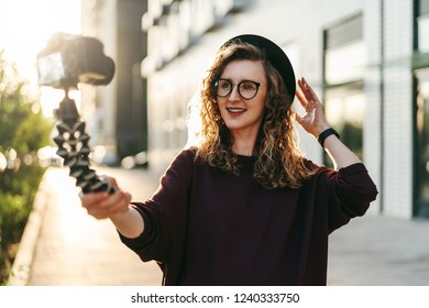 Young female blogger in trendy glasses and hat walks on city street, records herself on video holding camera for tripod. Hipster girl takes pictures of herself on camera. Lifestyle, selfie, backlight.