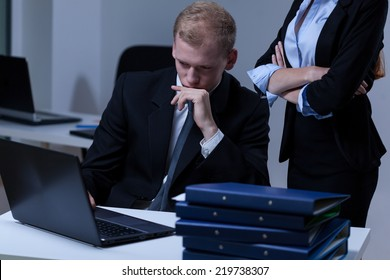 Young female boss checking his young attractive worker