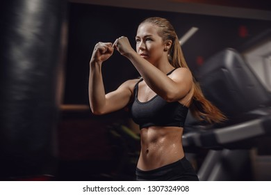 Young female boxer in motion to hit beats a punching bag. Concept boxing, fitness training.