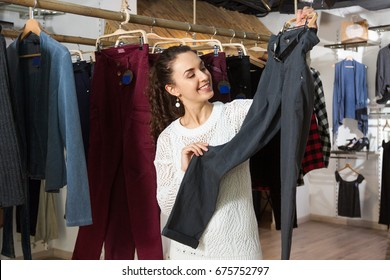 Young female brunette choosing new pants in store