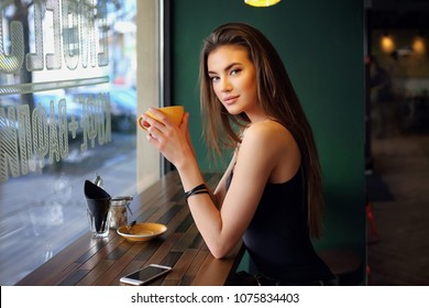 Young female brunette model sitting in cafe