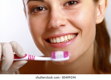 Young female brushing her teeth isolated on white background