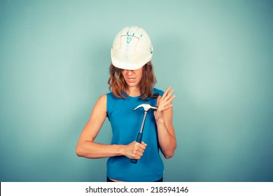 A young female builder is holding a hammer