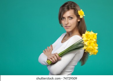 Young female with bunch of flowers over her shoulder on turquoise background