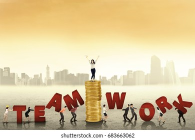 Young female business leader standing on a pile of gold coins while giving a command on her team to create a word of teamwork