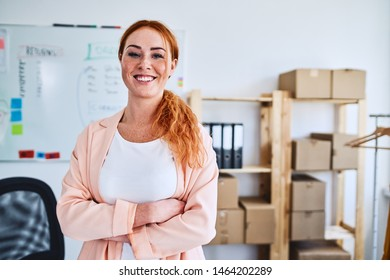 Young female business owner standing proudly with arms crossed and smiling at camera