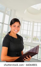 Young female business professional in modern office building holding a  leather folder. She is smiling in 3/4 view. Vertical format.